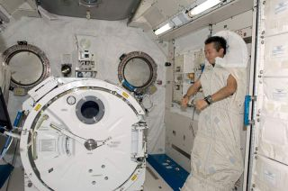 Japanese astronaut Koichi Wakata is photographed in a sleeping bag attached to the racks in the Kibo laboratory of the International Space Station.