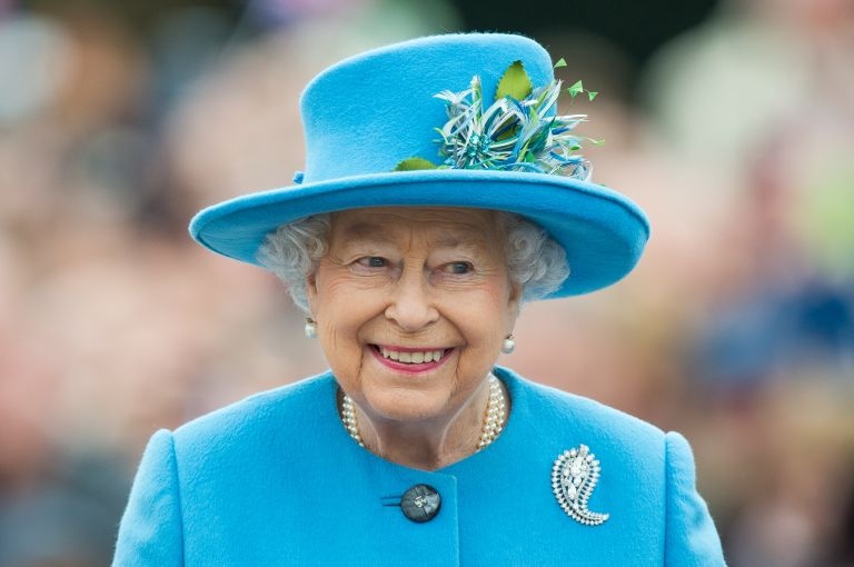 queen elizabeth in a blue jacket and hat
