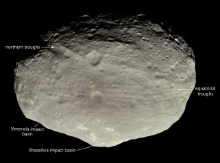 An image of the asteroid Vesta shows large impact basins and troughs.