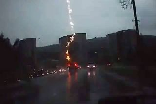 A screengrab from the YouTube video that apparently depicts an SUV being struck by lightning.