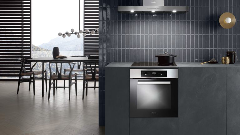 Miele kitchen appliances including oven and hob extractor hood with dining chairs in background