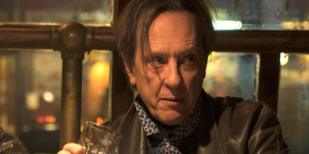 Richard E. Grant enjoying a drink in Can You Ever Forgive Me?