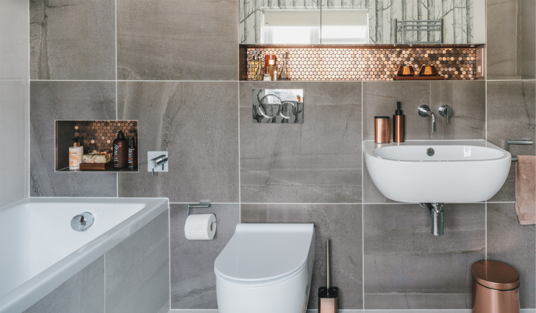 bathroom makeover grey tiles bathroom with copper accent tiles, a while freestanding basin and built in bath