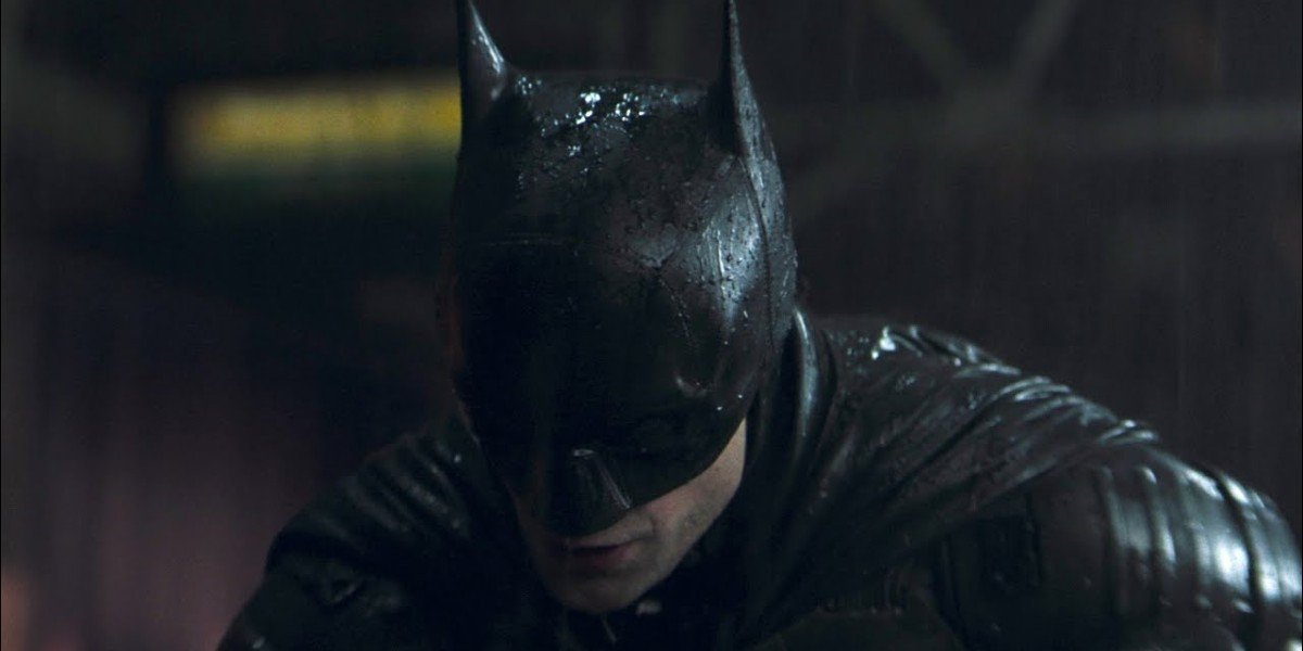 Batman (Robert Pattinson) stands over a thug in the rain in The Batman (2022)