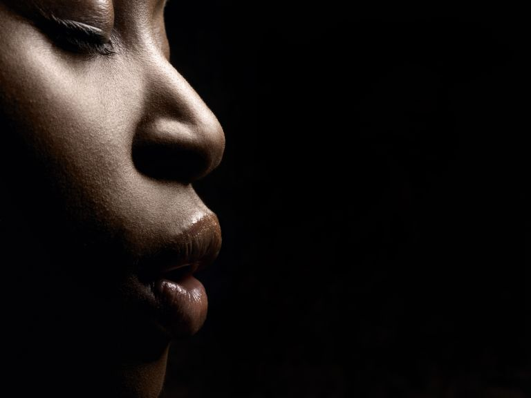 Cropped photo of a Black woman's face looking right against at black background