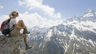 how to break in hiking boots: hiker on a rock outcrop