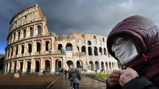A man wearing a protective mask passes by the Coliseum in Rome on March 7, 2020, amid fear of the COVID-19 epidemic.