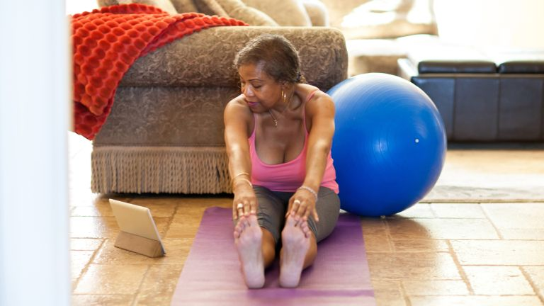 older woman touching her toes and stretching