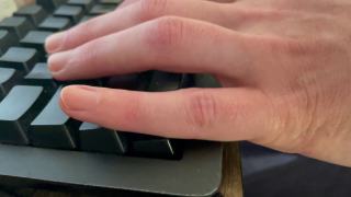 A hand with fingers on the keys W, A, S, and D, with the lower part of the pinky pressing down on Ctrl.