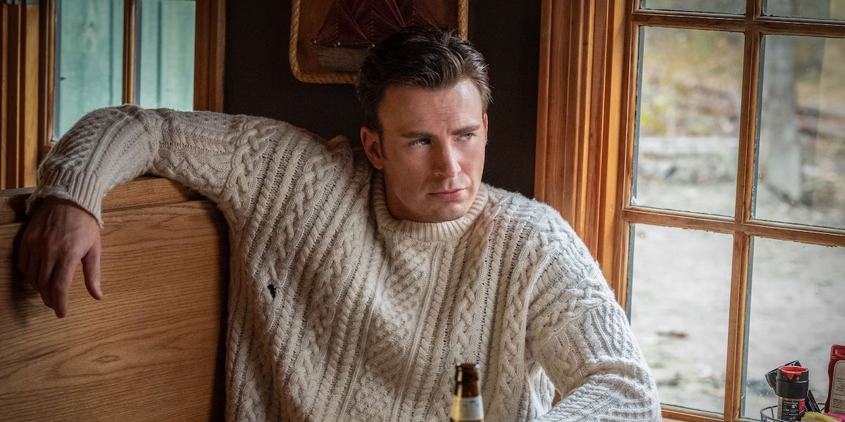 Ransom Drysdale (Chris Evans) wears a now-infamous cable knit sweater while leaning back in a booth