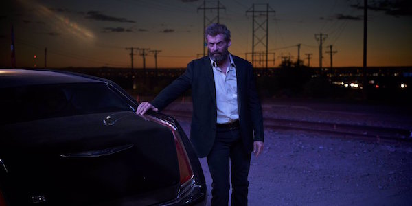 Hugh Jackman as Wolverine next to limo in Logan