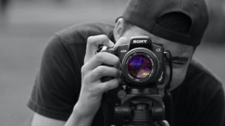 Best website builder for photographers: Man taking photo using Sony camera on tripod