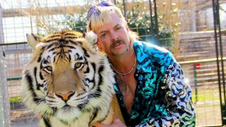 "Joe Exotic of ""Tiger King"" poses with a tiger."