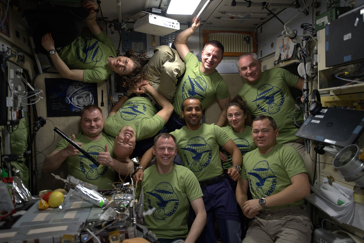 "The International Space Station's nine-person crew of Expedition 60 poses in ""space band"" shirts in this photo shared by European Space Agency astronaut Luca Parmitano (upside down) on Sept. 30, 2019. The shirts say ""Kryk Chayky"" (Cry of the Seagull in Russian)."