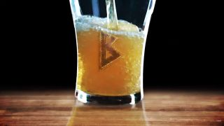 A glass of beer with a runic B.