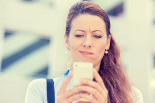 A woman looks confused while looking at her smartphone.