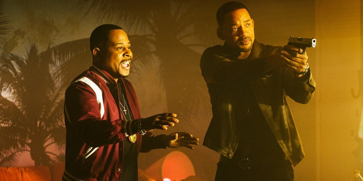Marcus Burnett (Martin Lawrence) holds his hands out while Mike Lowrey (Will Smith) aims his gun in