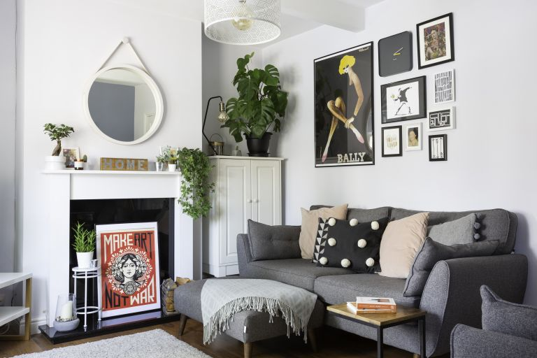 Scandi style Living room with light grey walls, original brown floorboards, grey sofa and matching footstool covered in pastel pink and black cushions and gallery wall