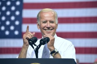Joe Biden gestures in front of an American flag
