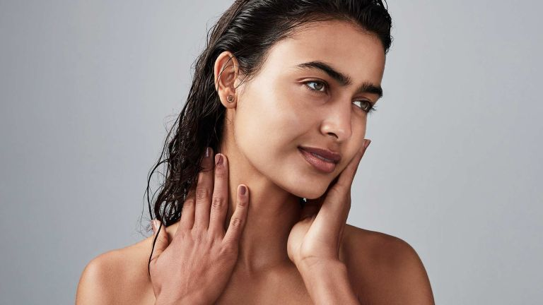 A woman is pictured with wet slicked back hair and brighter, glowing skin, presumably after using one of the best vitamin c serums
