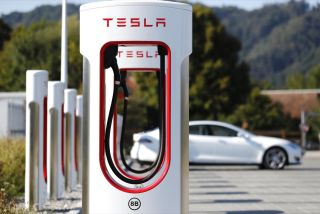 Photograph of a white Tesla model 3 charging through the supercharger.
