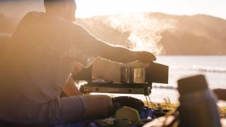 best camping stoves: A man preparing a meal on a stove