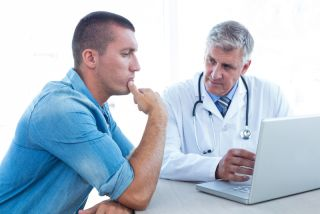 A doctor talks with a male patient.