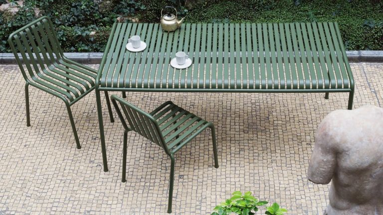 A green metal garden table and chairs on a paved courtyard with greenery behind