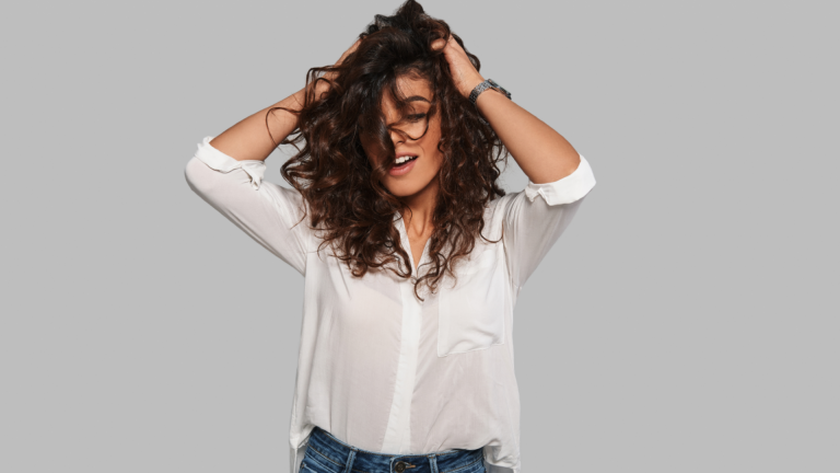 Woman touching her curly hair for a scalp massage