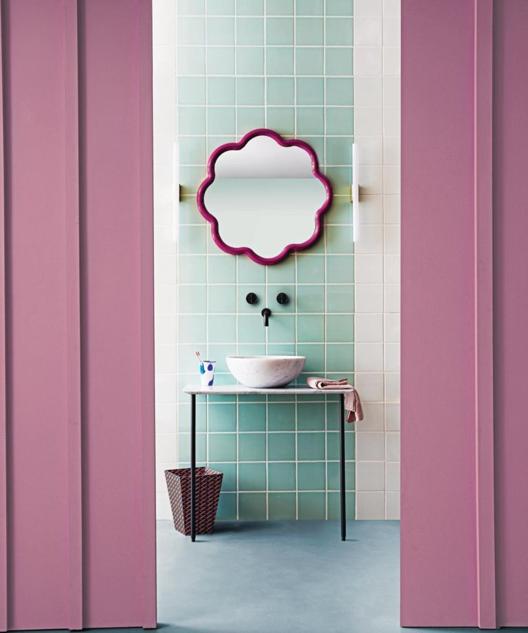 An example of bathroom color ideas showing a pink and green bathroom with a flower shaped wall mirror