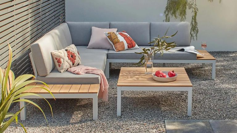 A contemporary wooden garden sofa with grey cushions on a gravelled patio