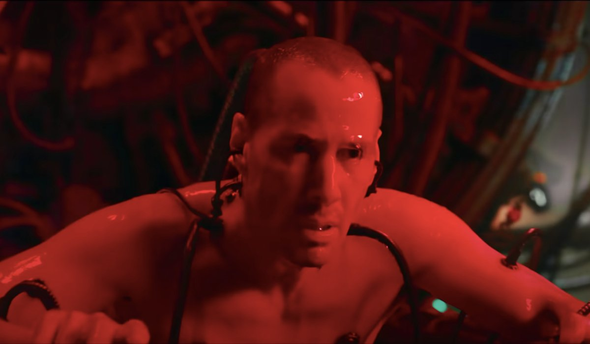 Keanu Reeves awakens connected to a machine pod in The Matrix Resurrections.