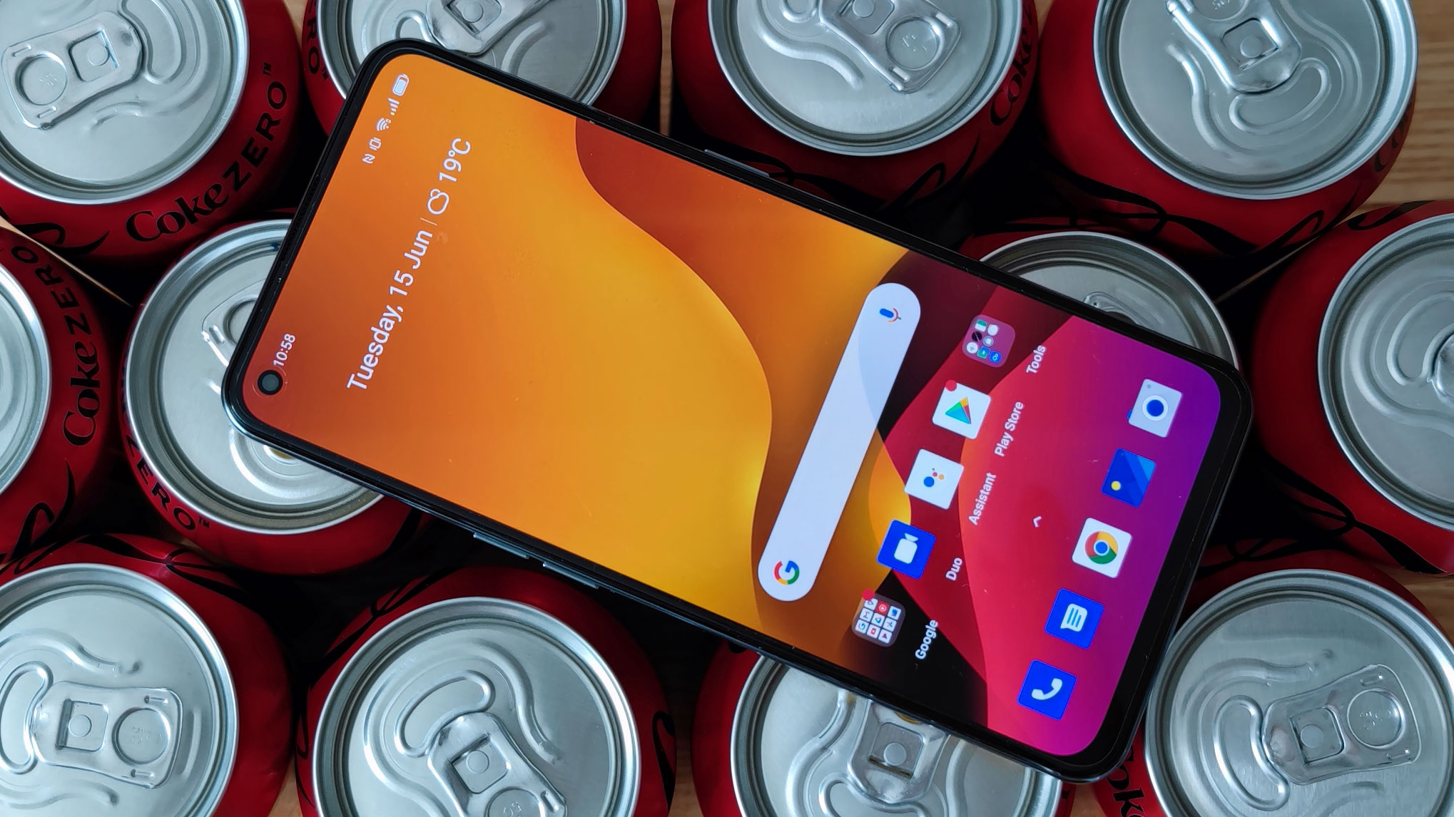 A Realme GT sat on top of some canned drinks