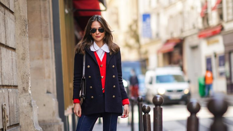 Therese Hellström wears Ray-Ban sunglasses, a white shirt with Peter Pan collar, a navy dark blue oversized military wool jacket with golden buttons, a red wool cardigan with golden heart-shaped buttons, a brown leather Hermes bag, blue denim jeans, beige quilted shoes, on March 19, 2021 in Paris, France