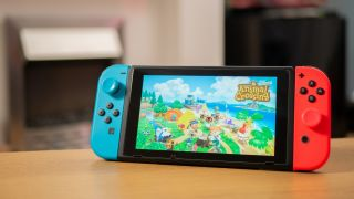 Nintendo Switch propped up on desk with Animal Crossing New Horizons image on screen.