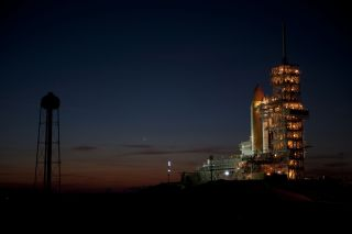 Space shuttle Discovery is photographed at sunrise at the launch pad before its final mission.