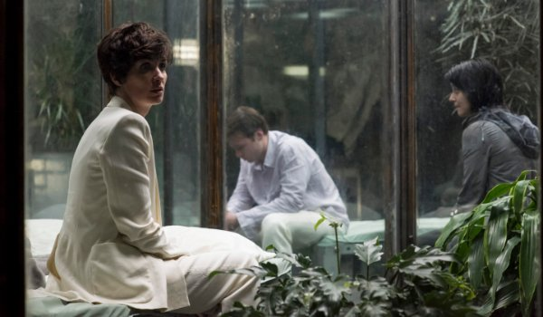 The OA Paz Vega sitting in a greenhouse, dressed in a white suit