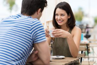 A woman and man talk over coffee.