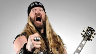 Black Label Society's Zakk Wylde pointing at the camera while holding a guitar