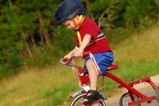 A little boy rides a tricycle, wearing a helmet