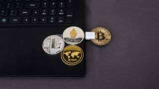 Image of pretend cryptocurrency coins on laptop and plugged in via USB
