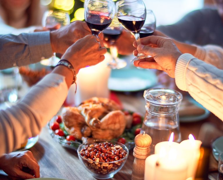 cheering over a christmas dinner table drinking wine