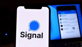 The Signal app logo displayed on an iPhone, with a screenshot of the Signal app in use displayed on a monitor in the background.