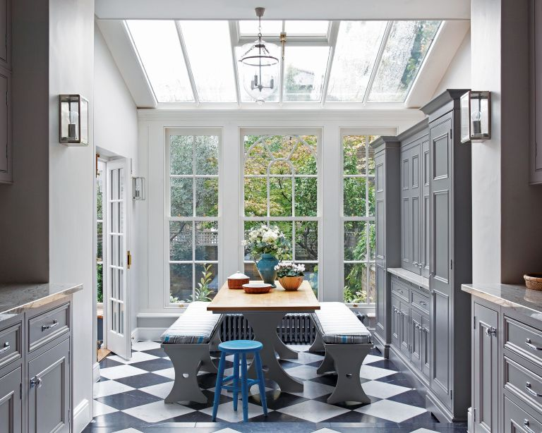 Gray kitchen cabinet colors with a skylight, large windows and dining area.