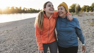 A young woman with blonde hair laughs and walks near a lake with her grandmother