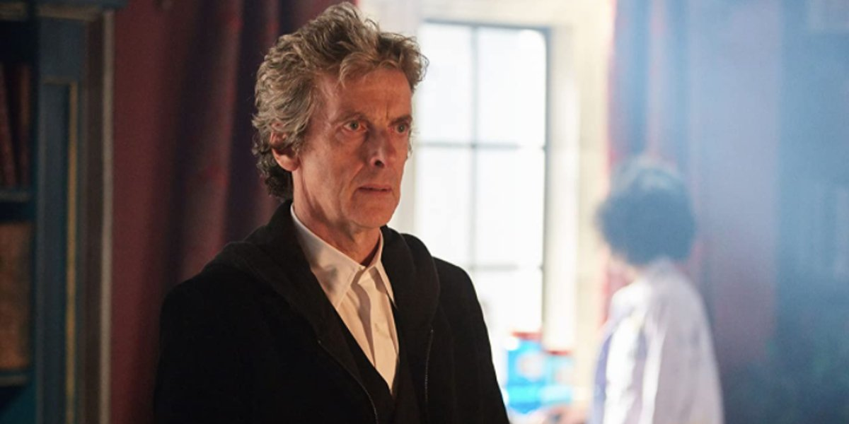 Peter Capaldi stands with a stern expression on his face in Doctor Who.