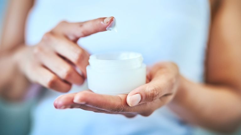 close up of woman's hands holding jar of face cream