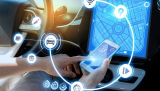 Driver setting up a wireless connection between a smartphone and an automotive infotainment system.