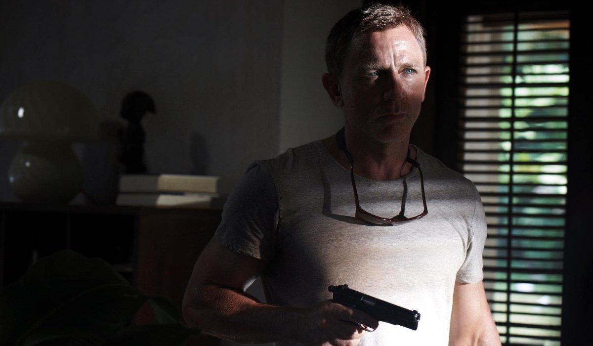 No Time To Die Daniel Craig in shadow, with his gun drawn