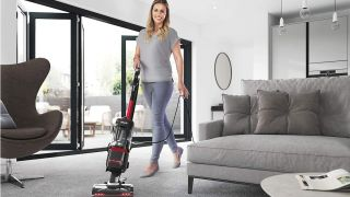 A woman using a Shark vacuum to clean her floors
